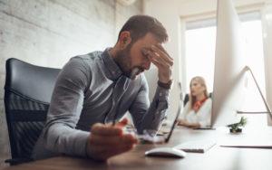 en mand med stress sidder på sin arbejdsplads
